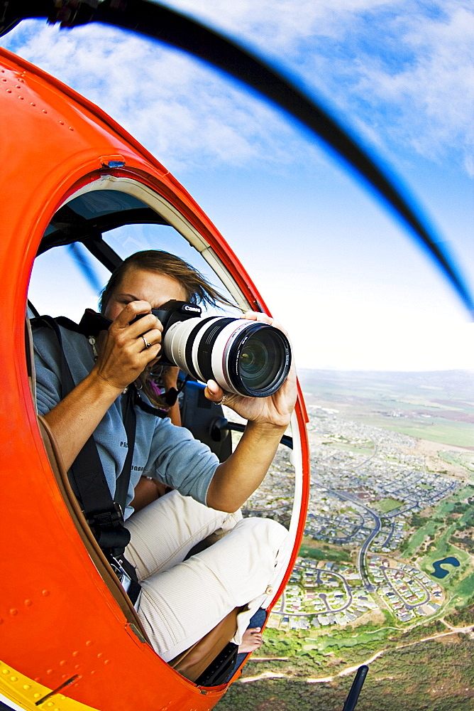 Hawaii, Maui, A female photographer shooting from a Helicopter.