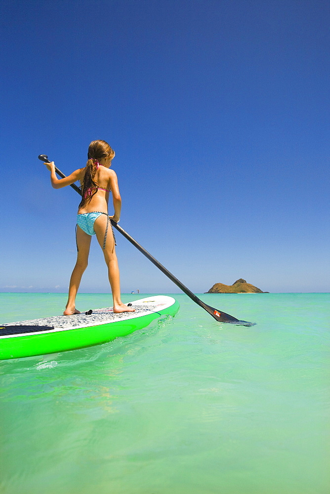Hawaii, Oahu, Lanikai, Young girl stand up paddling.