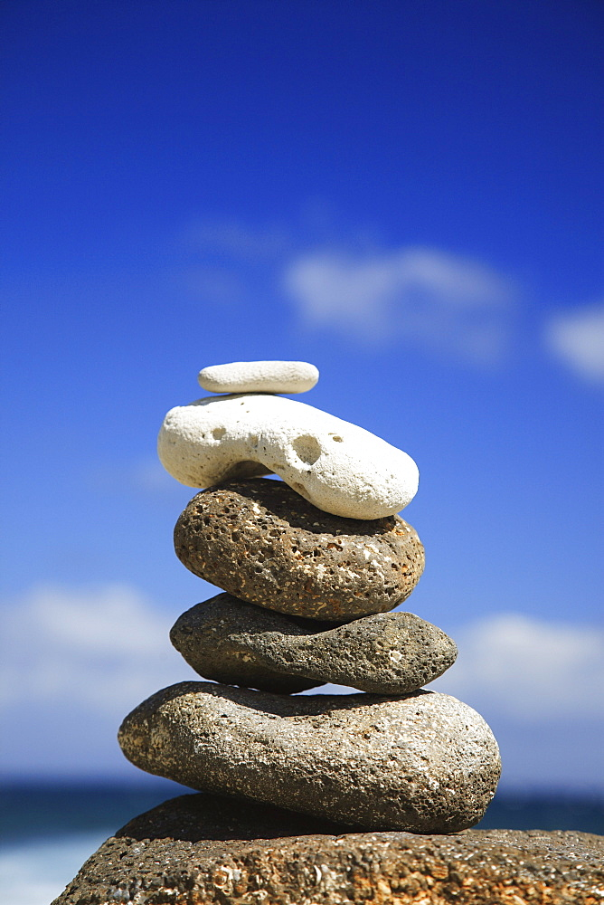Hawaii, Oahu, Spa element of rocks stacked up against a blue sky.