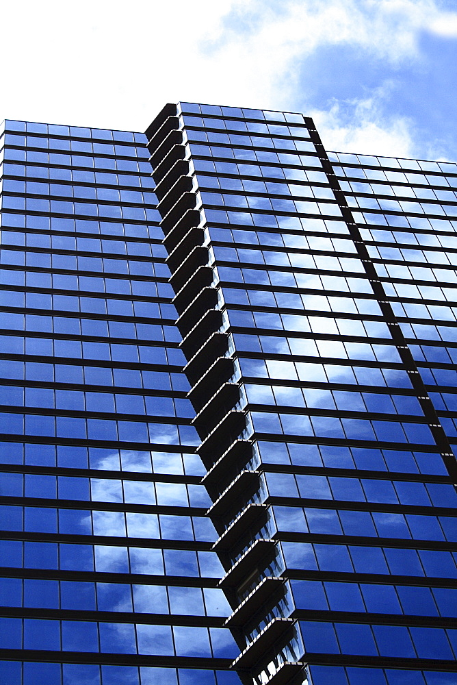 Hawaii, Oahu, Honolulu, Downtown financial district of a tower with the blue sky reflecting on windows.
