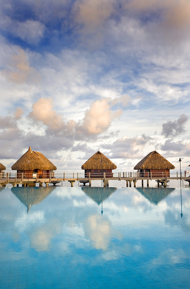 French Polynesia, Pearl Resort, Bungalows over beautiful turquoise ocean.