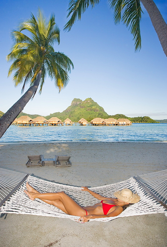 French Polynesia, Tahiti, Bora Bora, Woman resting in hammock with bungalows in the background.