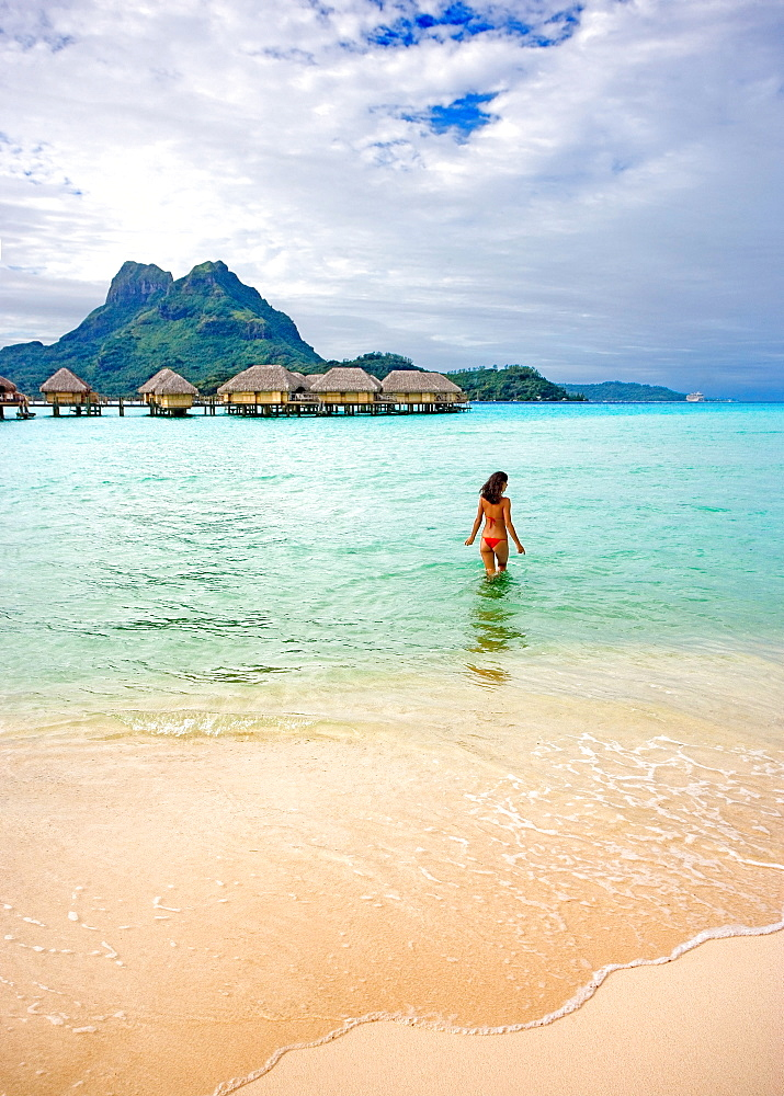 French Polynesia, Tahiti, Bora Bora, Woman in the ocean with bungalows in the background.