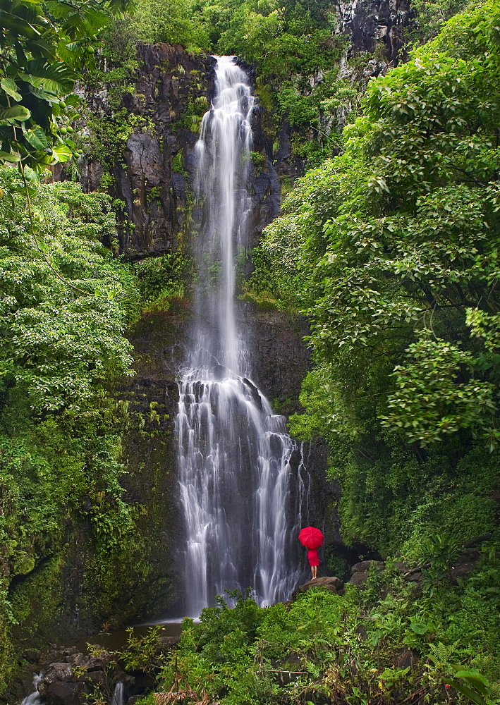 Hawaii, Maui, Kipahulu, Hana Coast, Woman stands with umbrella at Wailua Falls surrounded by foliage.