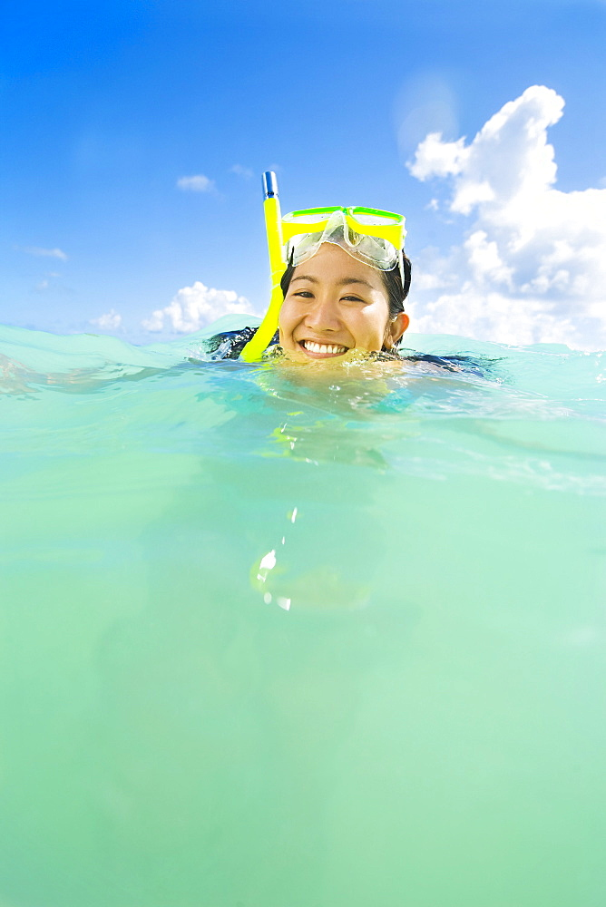 Hawaii, Oahu, Lanikai, Young Japanese woman wearing snorkle gear in the ocean.