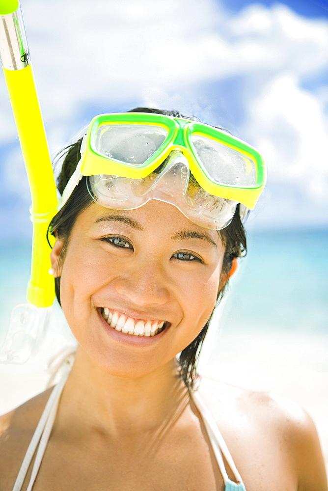 Hawaii, Oahu, Lanikai, Young Japanese woman wearing snorkle gear on the beach.