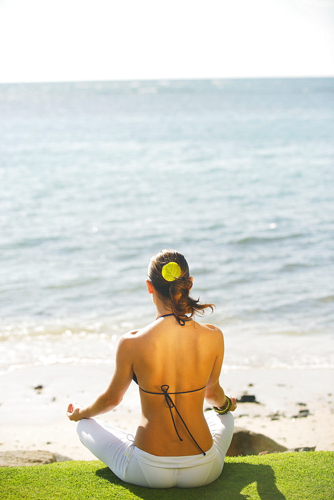 Hawaii, Woman meditating on grass near ocean, View from behind.