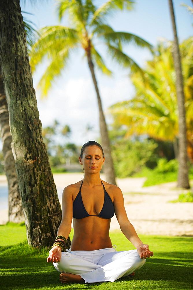 Hawaii, Woman meditating on grass near beach.