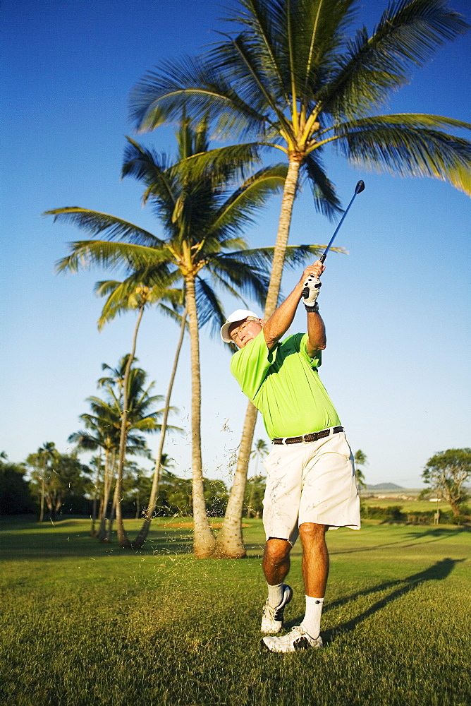 Hawaii, Maui, Male golfer swinging golf club at the Maui Country Club course.