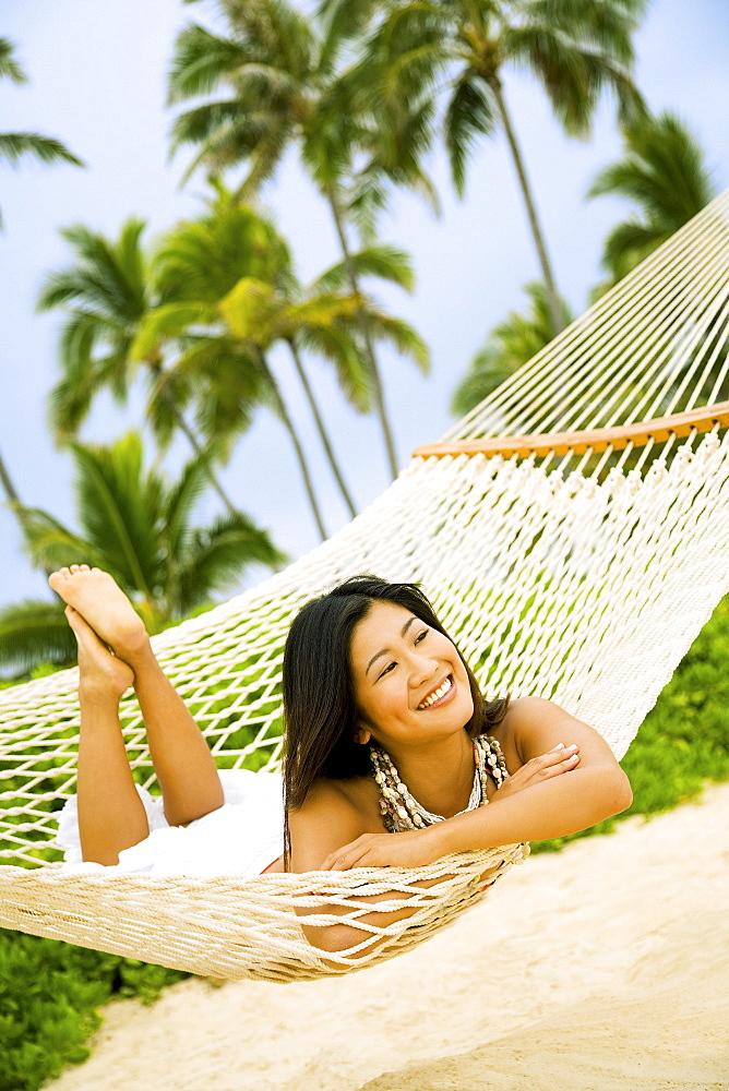 Hawaii, Oahu, Lanikai,  Japanese woman in hammock.