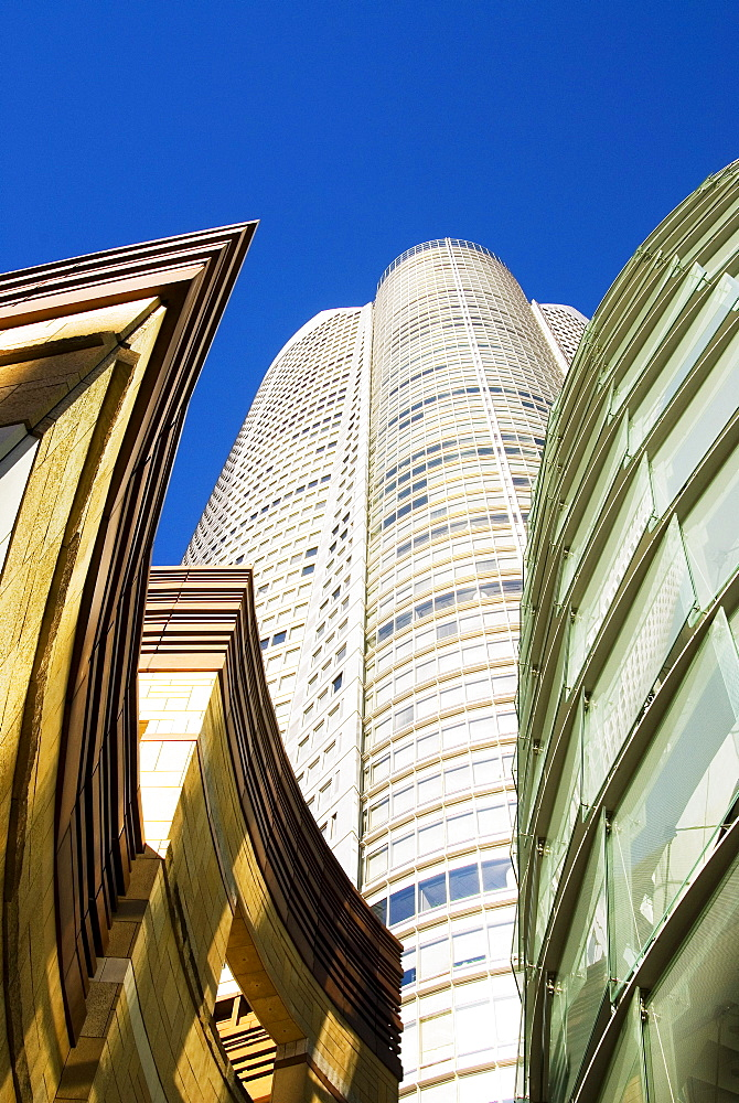 Japan, Tokyo, Roppongi Hills, upward view of Mori Tower framed by glass and stone of lower structures.