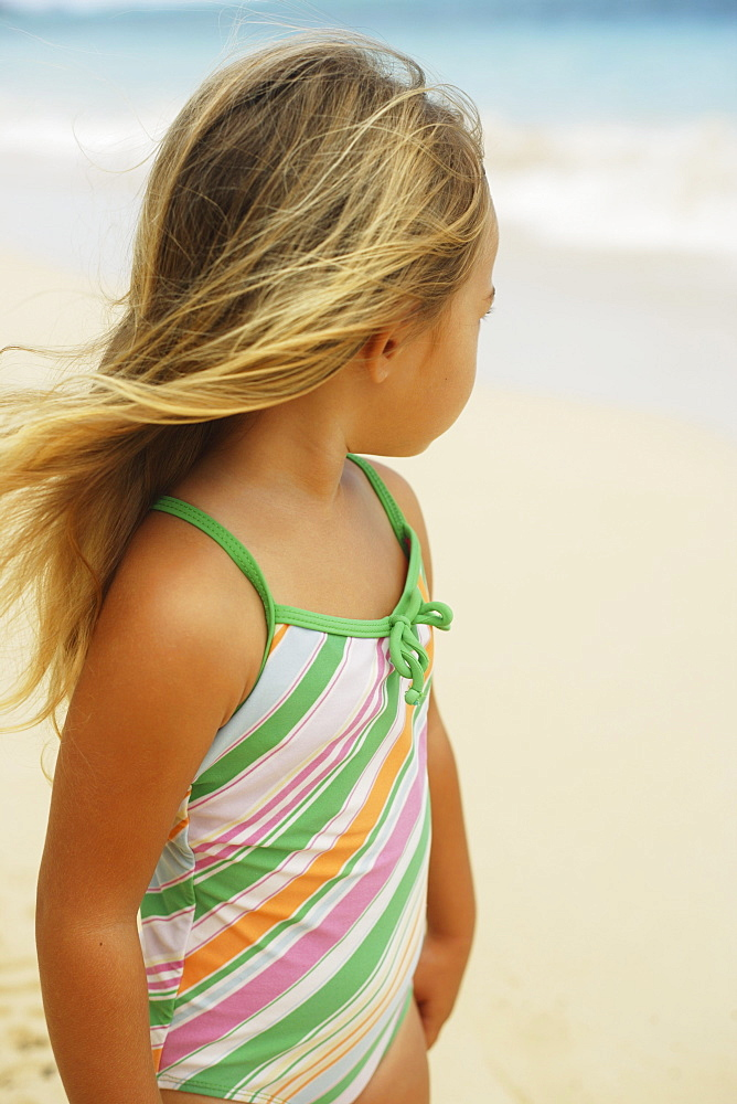 Hawaii, Oahu, little girl poses on beach.