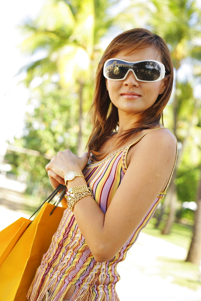 Hawaii, Oahu, Honolulu,  Young woman shopping at Ala Moana shopping center.