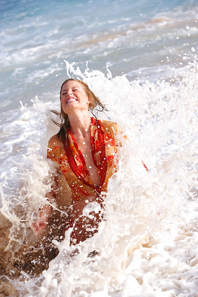 Hawaii, Oahu, girl getting splashed by a wave.