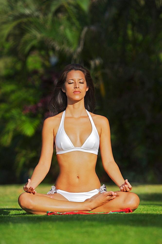 Hawaii, Oahu, Waikiki, woman doing yoga on grass at Kapiolani Park.