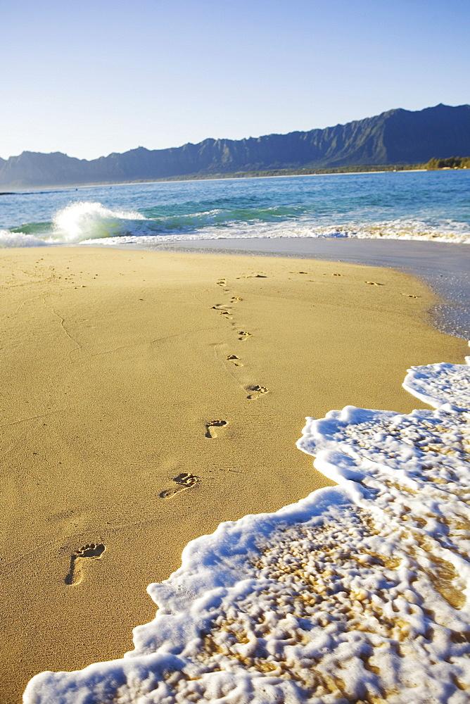 Hawaii, Oahu, Mokulua Island, footprints in the sand, water lapping on the beach, Koolau mountains in background.