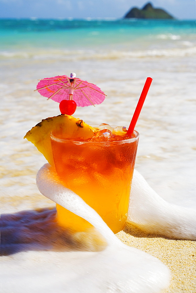 Mai Tai getting splashed by a wave as it rest on the beach.