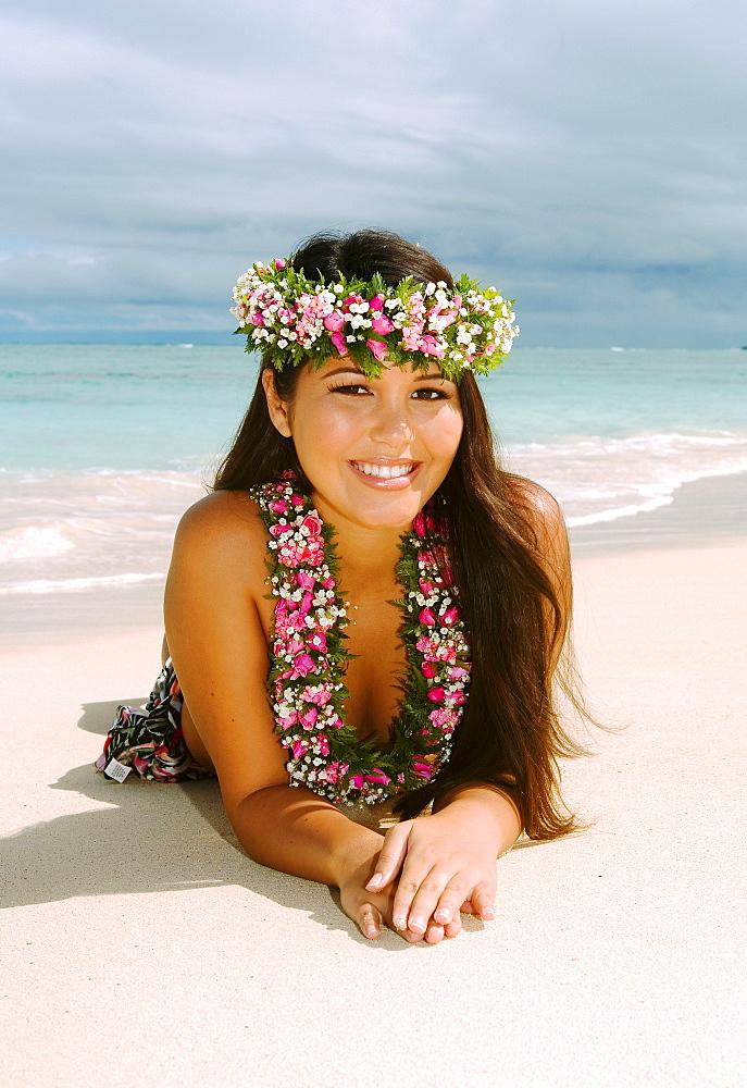 Hawaii, Oahu, Lanikai, Beautiful Hawaiian girl in haku and lei, laying on the beach.