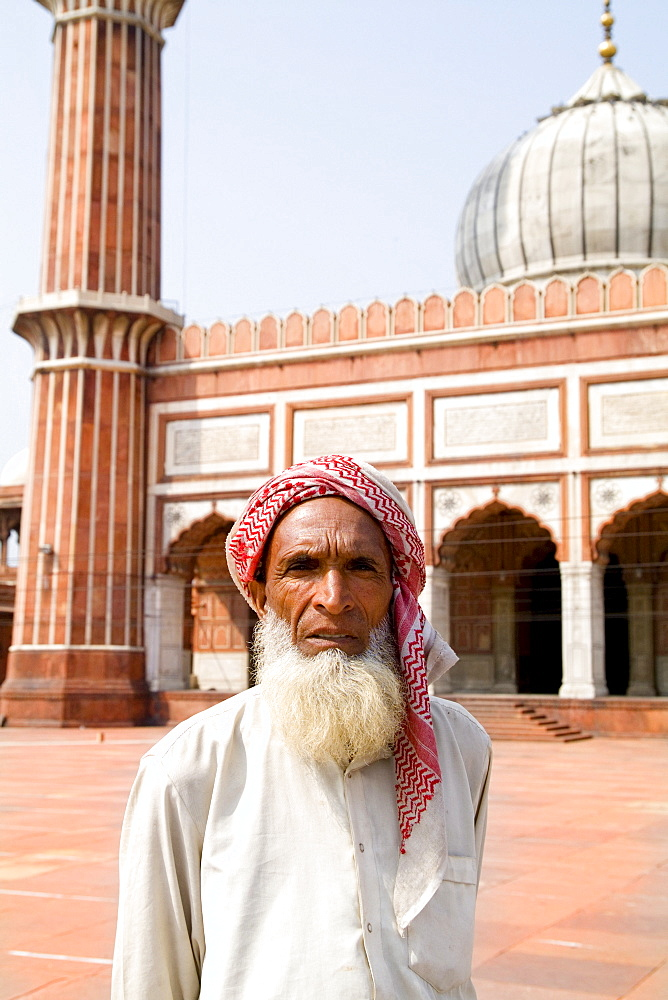 India, Delhi, Jama Masjid, a man standing within the largest mosque in the country.