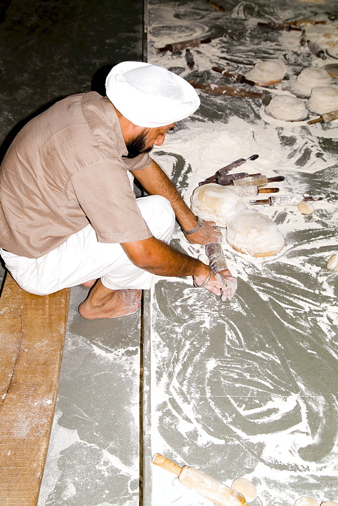 India, New Delhi, Bangla Shib Gurudwara, Sika Great Temple, man forming dough to feed members for free.