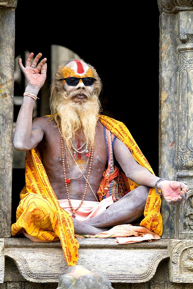 Nepal, Kathmandu, painted religious man wearing western sunglasses at Pashupatinath holy Hindu place on Bagmati River.
