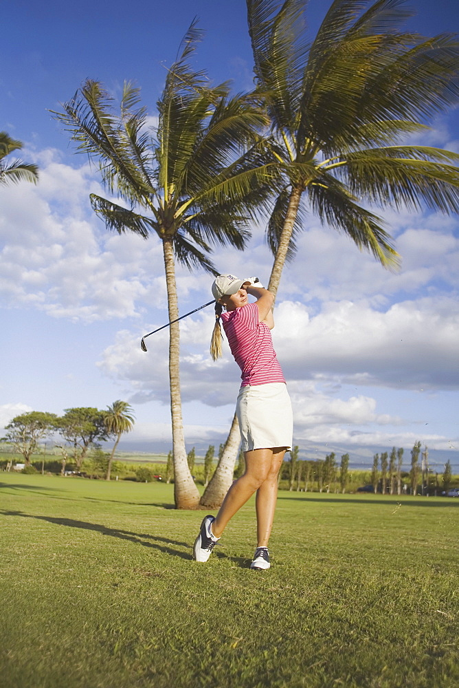 Hawaii, Maui, Wailea Gold Golf Course, Female golfer in midswing swing.