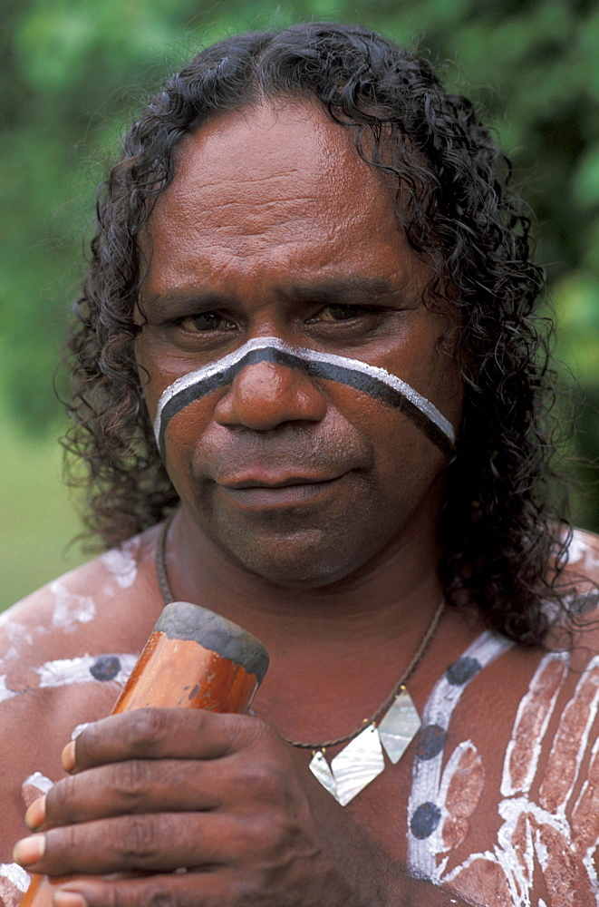 Australia, Queensland, Cairns,  Aboriginal native man holding didgeridoo, paint on body.