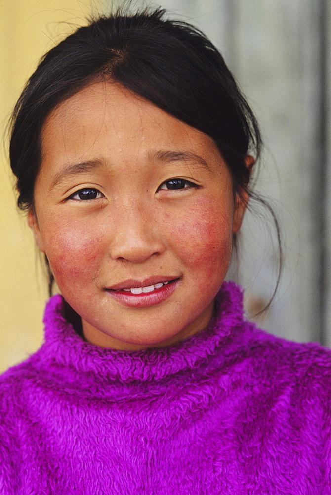 Mongolia, Ulaanbaatar, Headshot of young local girl in purple sweater.