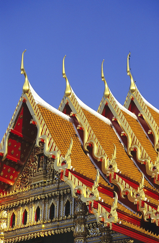 Bangkok, Thailand, Wat Benjamabophit (Marble Temple) top of gold trimmed temple, blue sky.