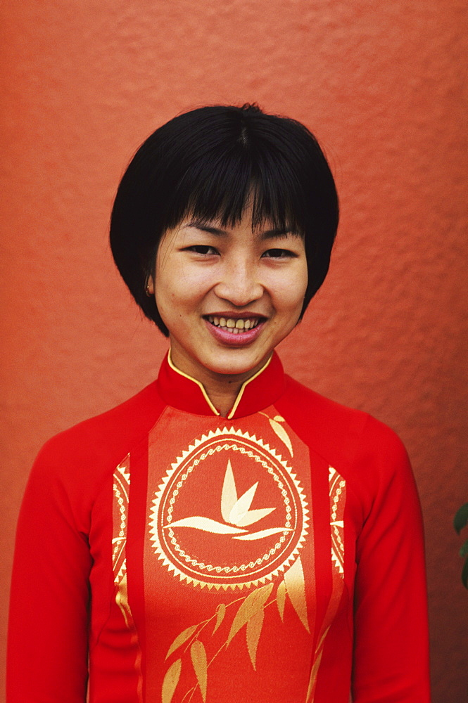 Vietnam, Ho Chi Minh City (Saigon), Portrait of beautiful local woman. dressed in red.