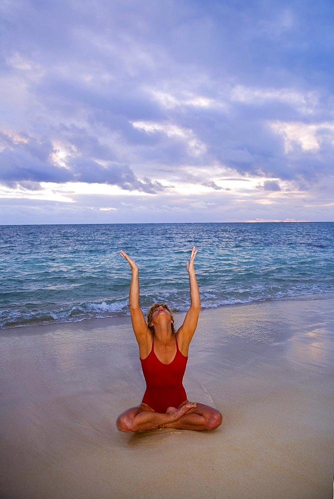 Hawaii, Oahu, Lanikai, woman doing yoga on the beach at sunrise.