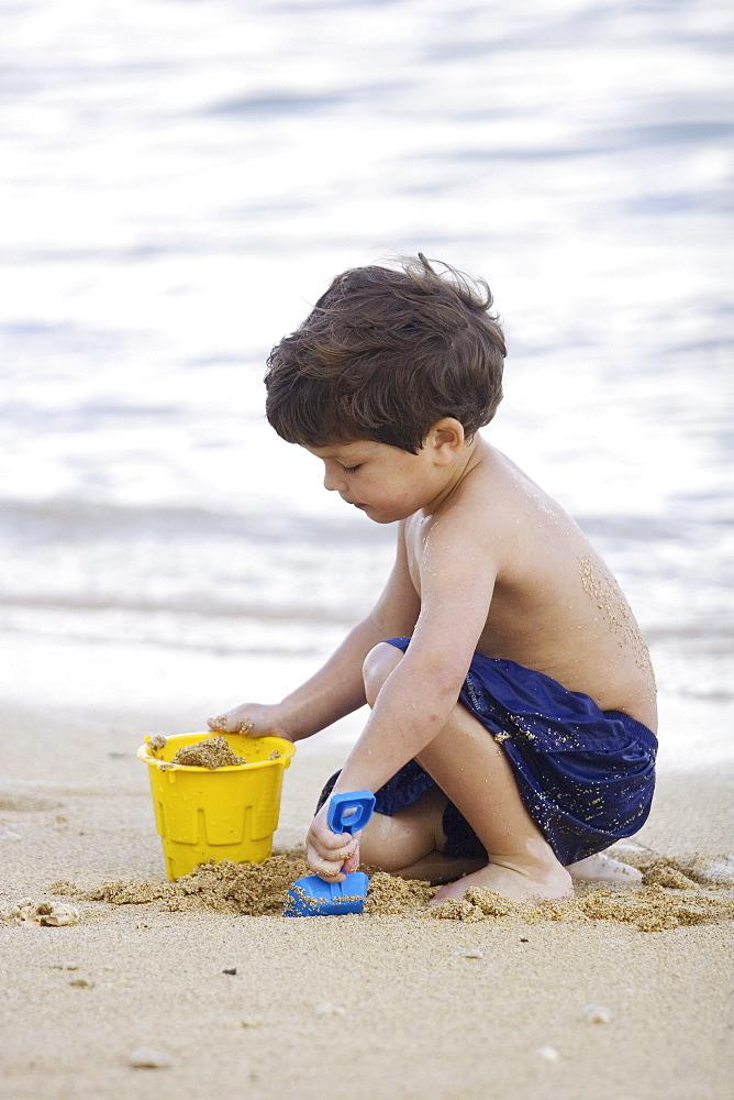 Hawaii, Maui, Spreckelsville, Baby Beach, Young boy playing in sand.