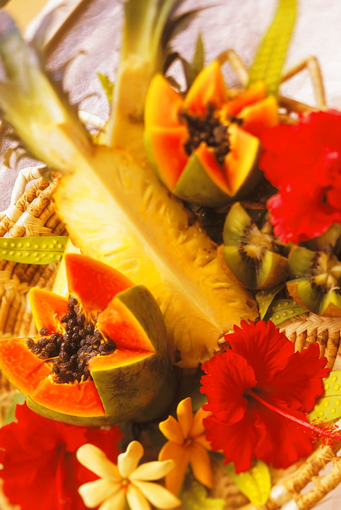 Colorful centerpiece with pineapple, papaya, kiwi, and hibiscus in woven basket