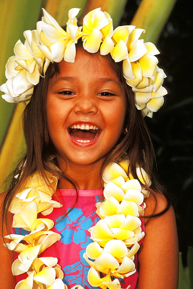 Close-up of young local girl with plumeria leis, greenery background