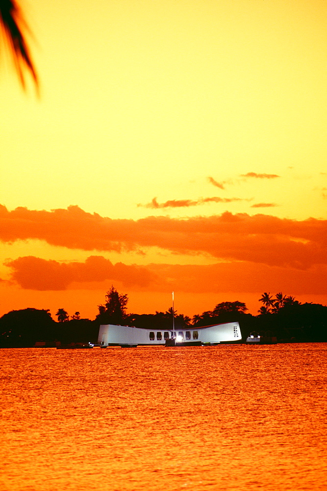 Hawaii, Oahu, Pearl Harbor, Full view of Arizona Memorial at sunset, bright orange yellow sky
