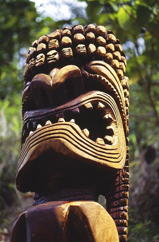 Hawaii, Oahu, Waimea Valley, Closeup of wooden tiki statue, greenery in background