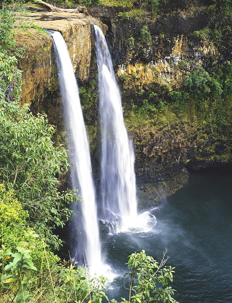 Hawaii, Kauai, Wailua Falls surrounded by foliage.