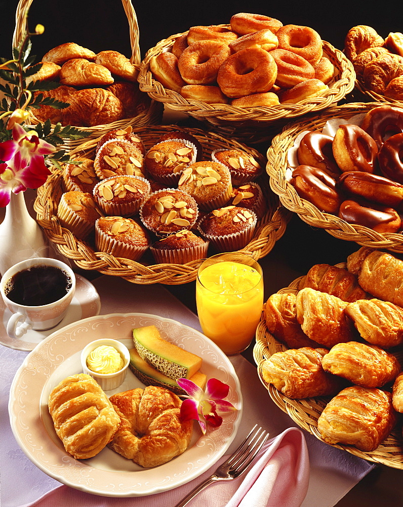 A breakfast selection of pastries with orange juice and coffee displayed on an elegant table.