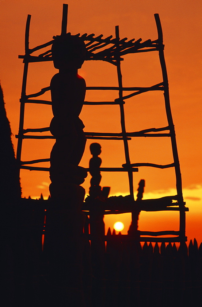 Hawaii, Big Island, Pu'uhonua O Honaunau National Historical Park, Structure and statues silhouetted by fiery sunset.