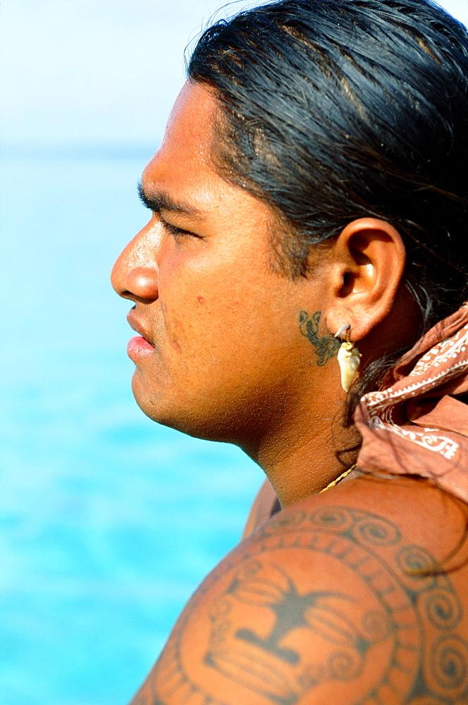 French Polynesia, Tahiti, Huahine,Tahitian man with tattoos, view from side