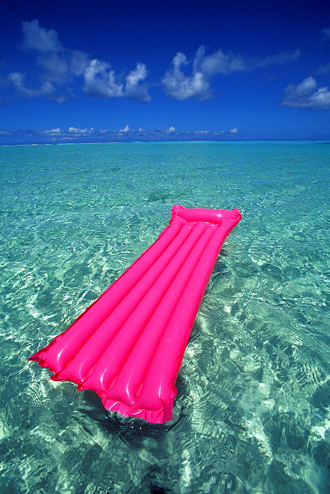 French Polynesia, Bora Bora, Pink inflated raft on clear ocean water seen from Bora Bora lagoon.