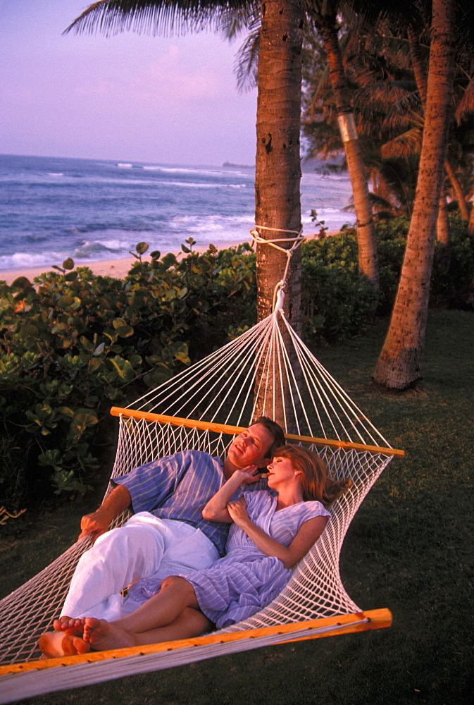 Couple at sunset, relaxing in Hammock in tropical setting. Hawaii