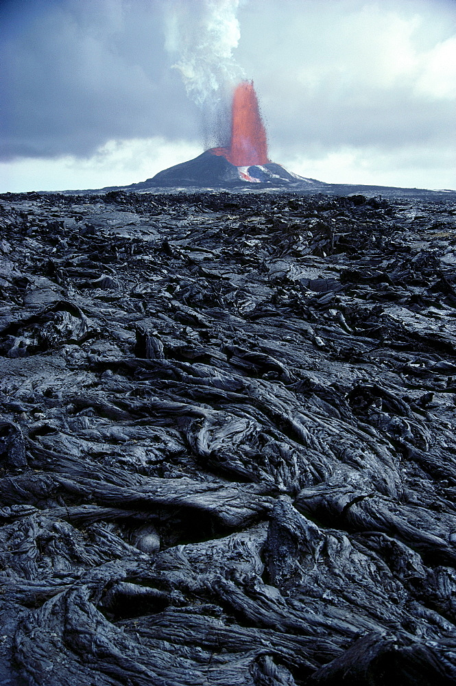 Hawaii, Big Island, Pu'u O'o eruption, pahoehoe lava in foreground, fountain background A27F