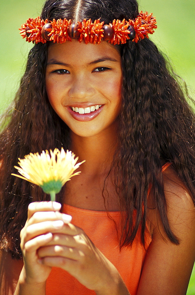 Young Hawaiian girl with orange haku holding flower.
