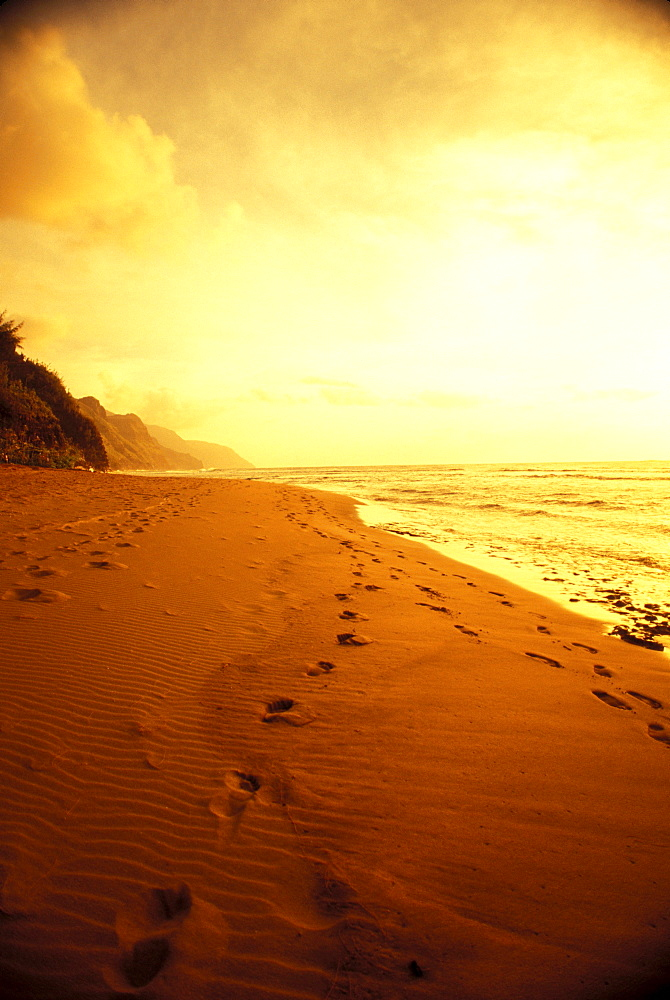 Hawaii, Kauai, Na Pali Coast, beach at sunset with footprints in sand, golden sky and water