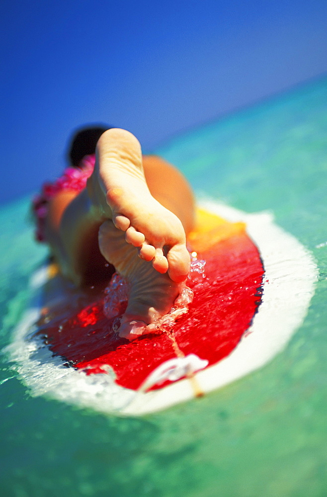 Hawaii, Oahu, Lanikai beach, close-up view from feet of woman with lei lying on surfboard