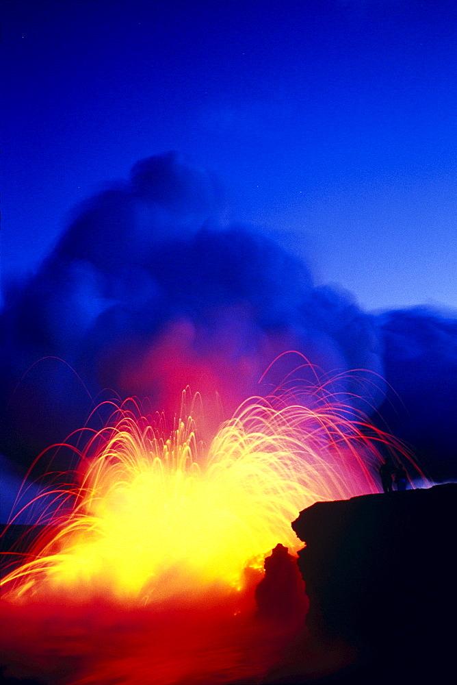 Hawaii, Big Island, Hawaii Volcanoes National Park, Lava explodes as flow hits ocean, fountain bright blue sky C1634