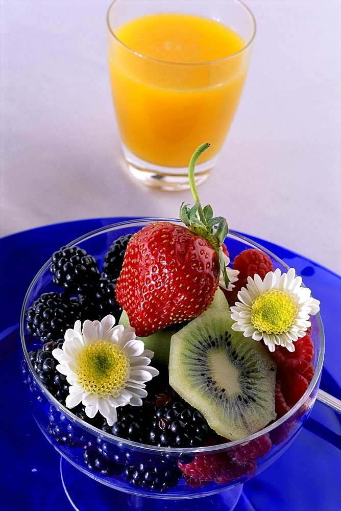 Close-up of a glass of orange juice with a bowl of fresh berries on blue dish