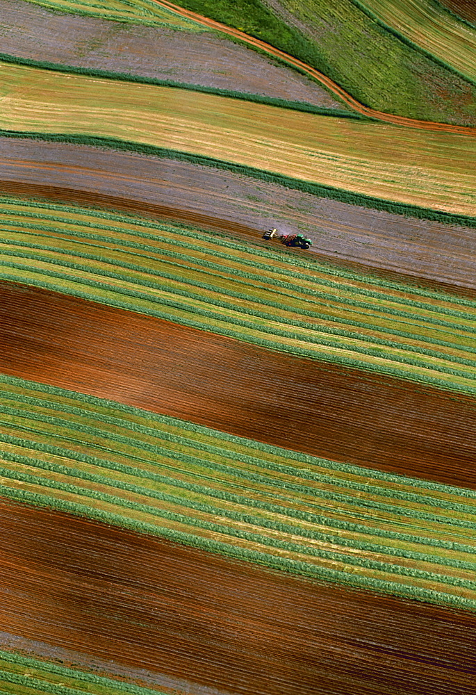 Agriculture - Aerial view of a tractor with an implement disking and planter planting in a single pass in contour strips / Virginia, USA.