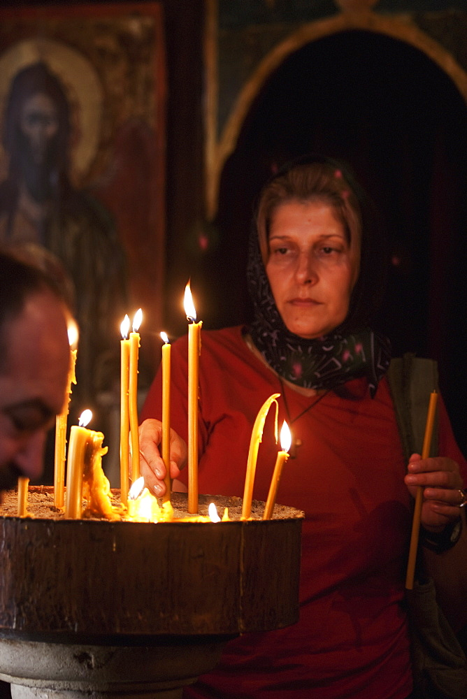 Woman Lighting Candles In The Church Of St. Nicholas, Kotor, Montenegro